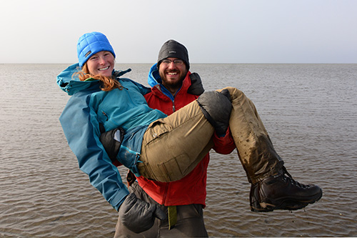 Brett Woelber and Chelsea Ward-Waller wearing Black Rock Gear down hats on the edge of the Arctic Ocean