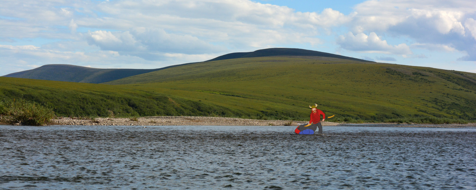Jason Mercer drags his Alpacka packraft over a shallow riverbar on the Anaktuvuk River, with the green hills of the North Slope and blue sky behind him