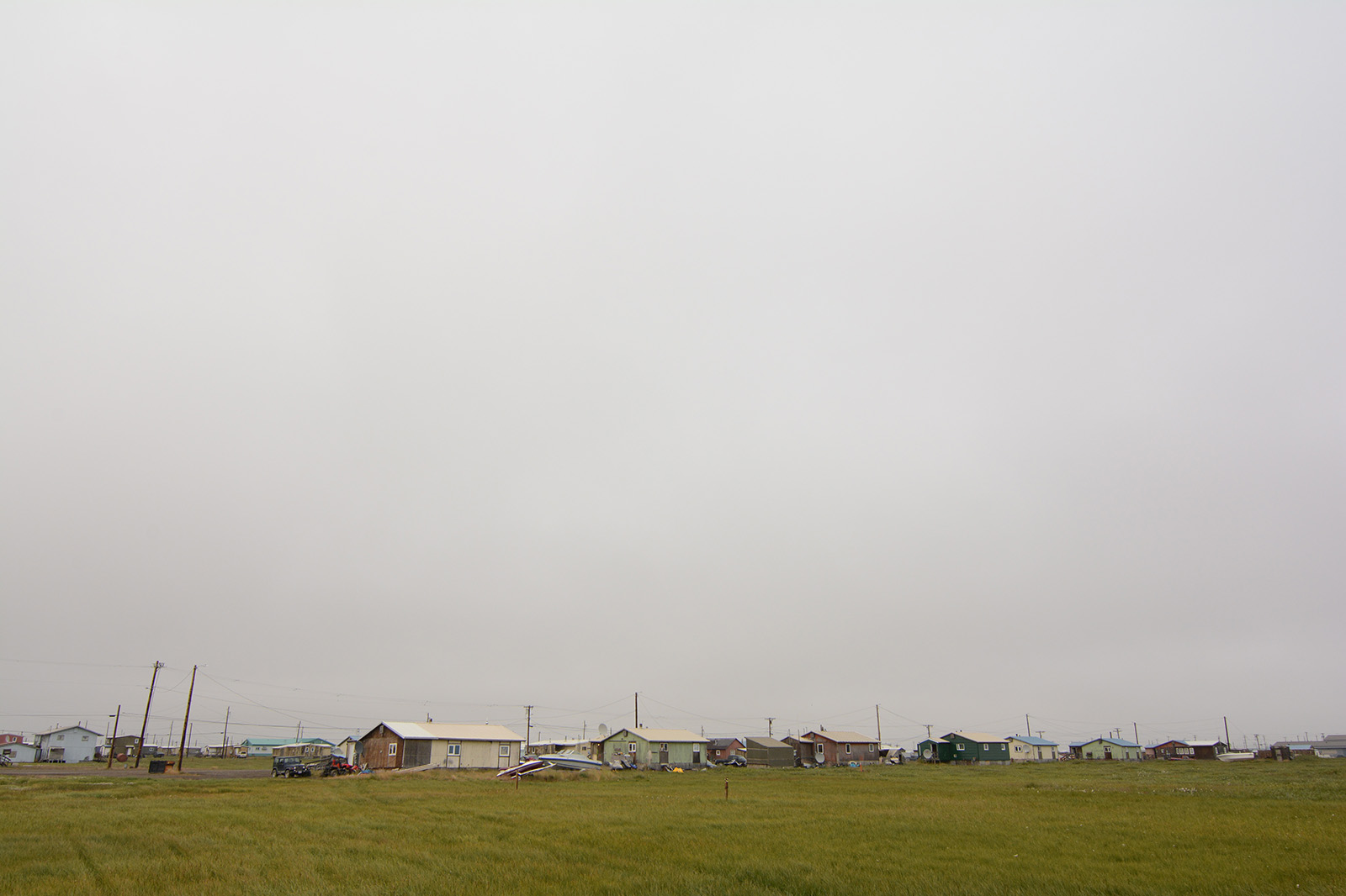 A row of small homes in Nuiqsut, Alaska, under an expansive gray sky