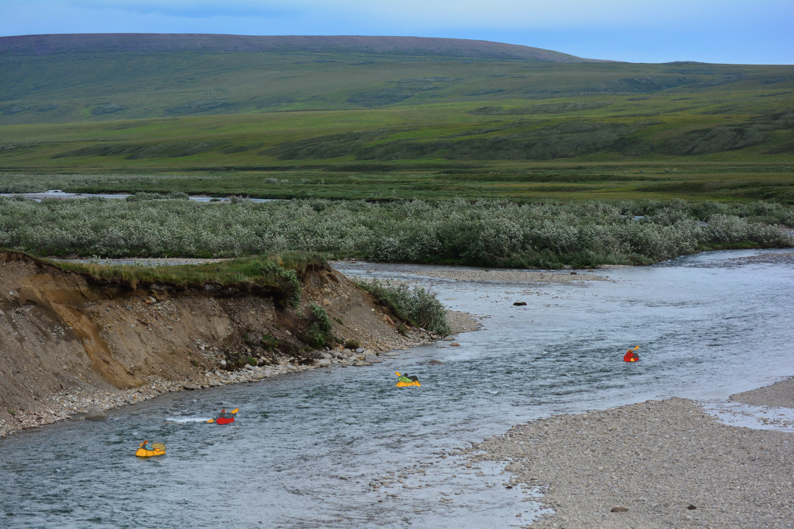 Four packrafters packrafting down the Anaktuvuk River, with the tundra hills of the North Slope in the background
