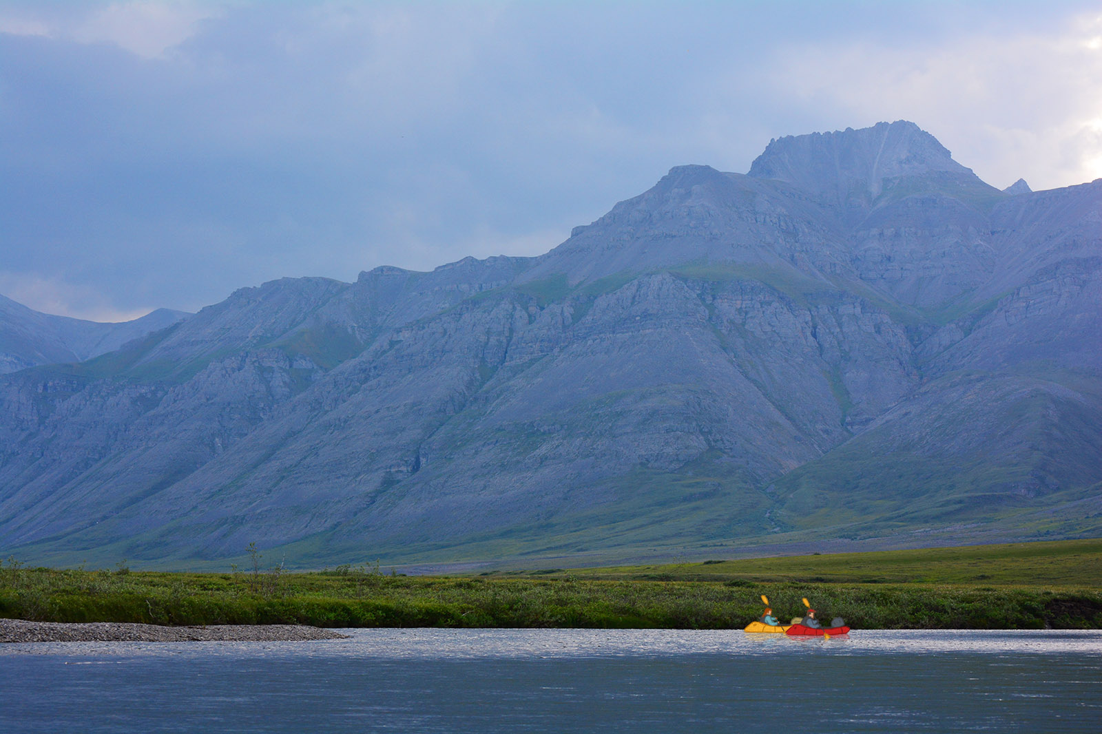 Brett and Chelsea packraft down the Anaktuvuk River below the Brooks Range Mountains in Alaska