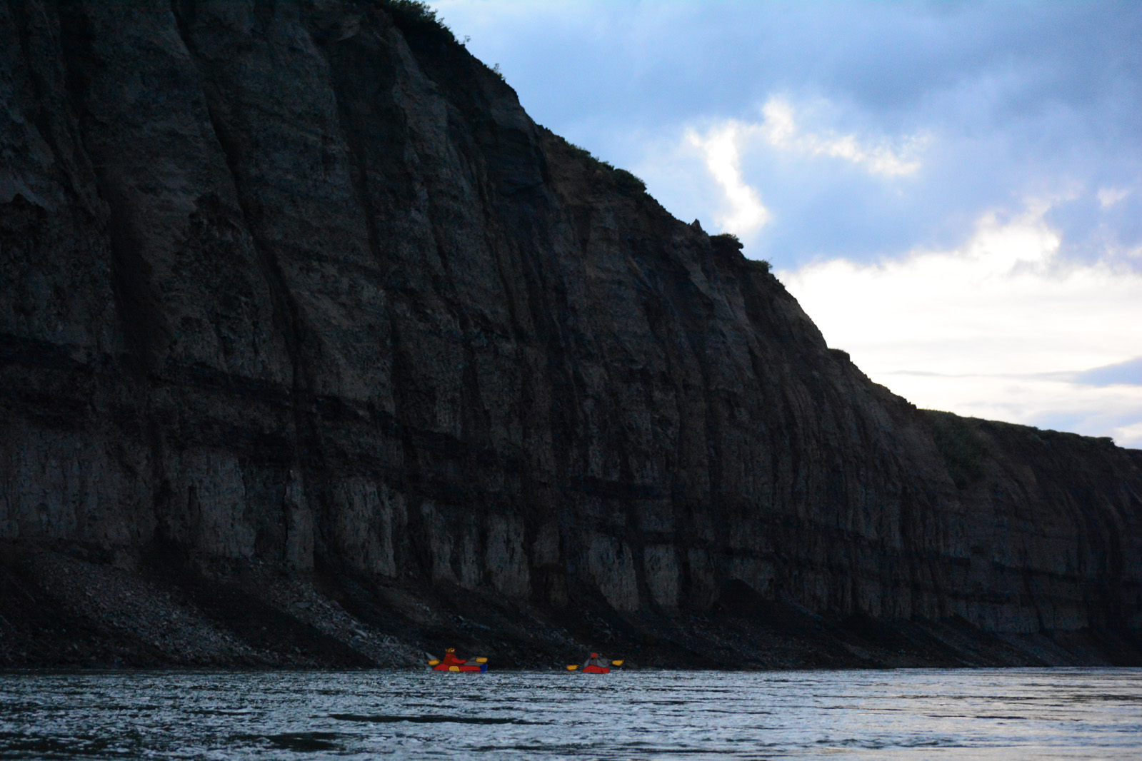 Two packrafters below the towering black bluffs of the Colville River at night