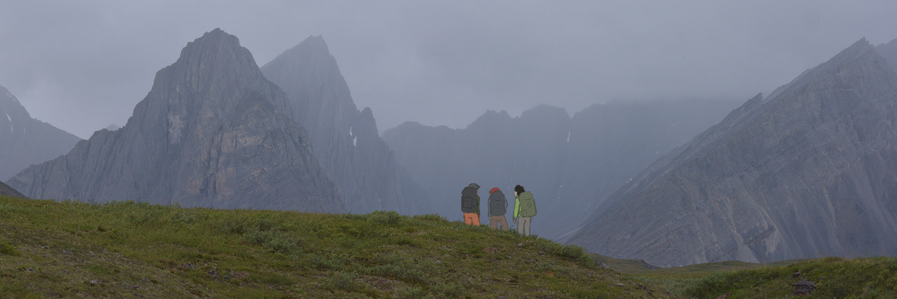 Three backpackers stand in front of tall, craggy mountains in the Brooks Range