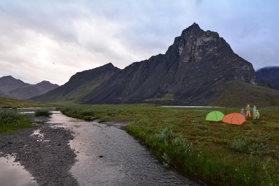 The tents and backpackers in Thunder Valley, beneat a large, steep mountain in the Brooks Range